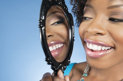 African American lady looking at her smile in a mirror.