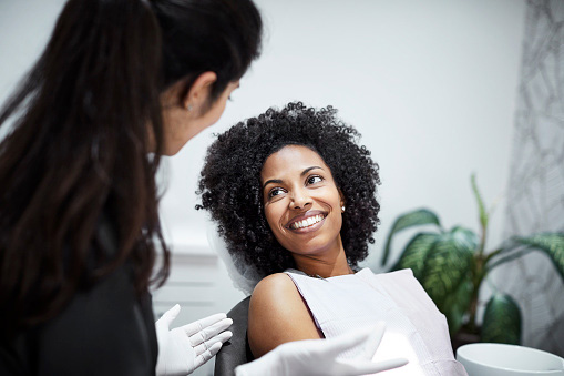 Beautiful Black woman talking to Dentist about bone grafting at David R. Moyer Cosmetic & Family Dentistry in Phoenix, AZ